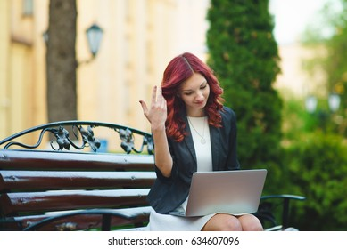 Girl with red hair with a laptop on the bench in the park