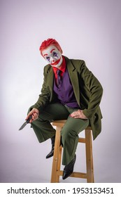 A girl with red hair in makeup and the image of an evil clown is sitting on a bar stool with a knife in her hand. Psychopath, maniac, horror movie. An evil clown or mime. Joker