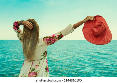 girl with a red hat in her hand on the coast admires the blue sea. Girl with raised hands standing by the sea. Back view