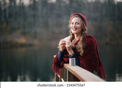 Girl in a red hat with a mug and a sandwich on the lake in autumn