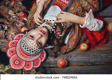The girl in the red headdress and Russian folk style among apples on dark wooden background top view