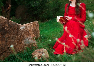 girl in red historical dress reading a book in the park