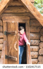 girl in red jacket and blue jeans is opening a wooden door of a small log house at the public playground.