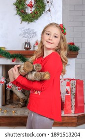 A girl in a red jacket at home. it stands next to the fireplace. Birch wood in the hands of the model. the fireplace is decorated with Christmas gifts. the new year is coming soon.