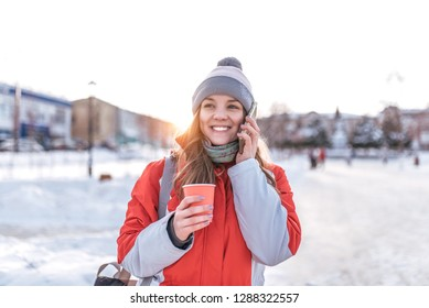 The girl in the red jacket in winter. In his hands holding a smartphone, happy and cheerful talking on the phone. Holds a cup of coffee or tea. In the early morning breakfast on the road.
