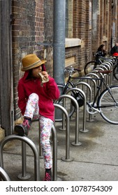 Girl with a red jumper sitting on the bicycle racks