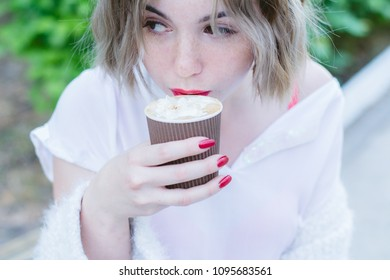Girl with red lips drinks cappuccino