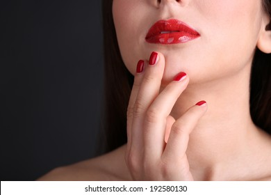 Girl with red lips and nails on dark background
