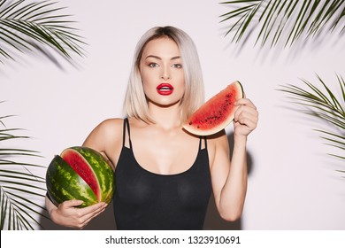 Girl with red lips posing at white studio background with palms, holding watermelon and looking at camera.