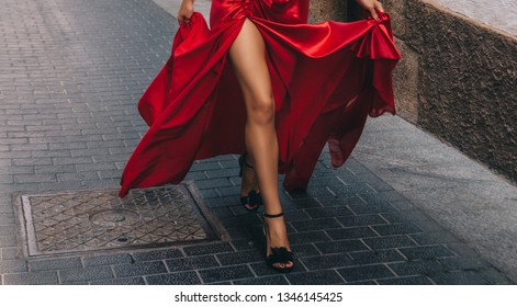 Girl in red. A girl with long slender tanned legs. In black high-heeled shoes. A girl in a long red dress running down the street. Slender Sexy legs.