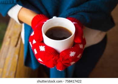 girl in red mittens holding a cup of coffee.