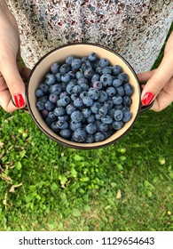 Girl with red nails holds bowl full of ripe blueberries. Vertical orientation. Green grass background.