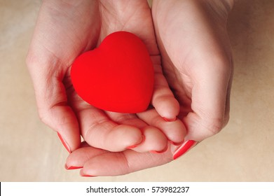 Girl with red nails shows a red decorative heart