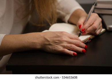 girl with red nails writing in a notebook