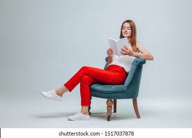 Girl in red pants sitting in a chair and reading a book with a white cover