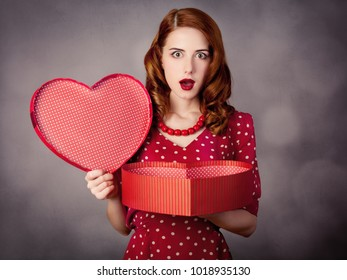 Girl in red polka dot dress with heart shape box for Valentine Day Holiday on grey background