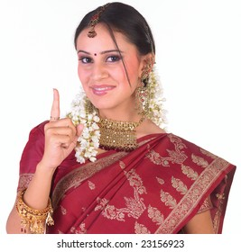 Girl with red sari showing one finger