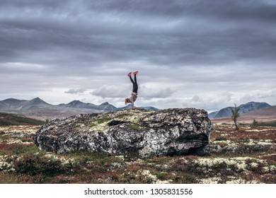 Girl with red shoes doing a handstand in nature on a big rock. Mountain scenery backdrop.