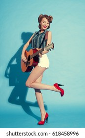 the girl in red shoes with guitar on blue background