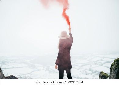 Girl with red smoke bomb. Emergency flare signal, smoke signal