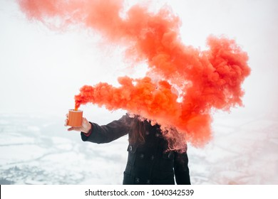 Girl with red smoke bomb. Hipster girl send smoke signal. Emergency flare signal, smoke signal