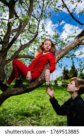A girl in a red suit is sitting on a branch and a young man holds out his hand to her