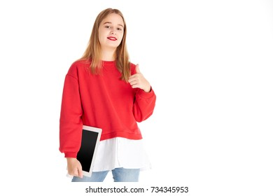 Girl in red sweater smiling and holding tablet on white background isolated