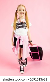 Girl with red tails on a pink background. A charming girl in bright sports clothes is holding a suitcase by the handle.