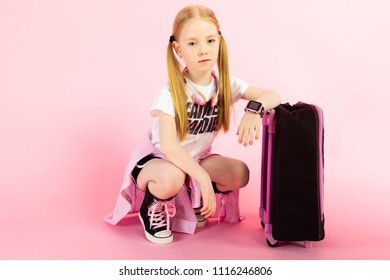 Girl with red tails on a pink background. A charming girl in bright sports clothes sits next to the suitcase.