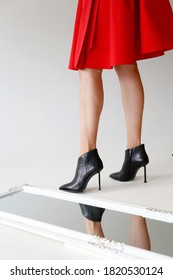 A girl in a red trench coat and black stiletto heels. Girl's legs in black stiletto heels. Legs of a girl in black high heel shoes on a white background.