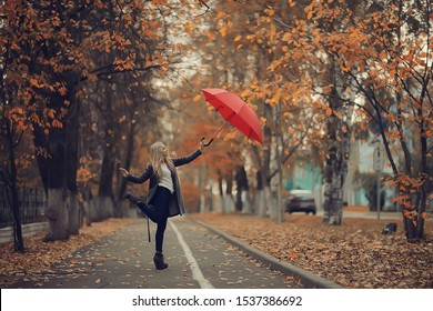 girl with a red umbrella, flying on an umbrella, jumping and having fun in a yellow autumn landscape