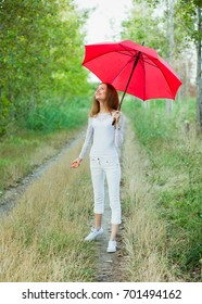 Girl with red umbrella is happy for the rain