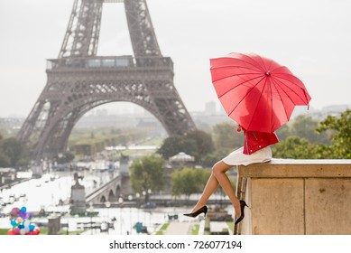 Girl with red umbrella sitting on the roof top of the Trocadero place in Paris and looking at the Eiffel tower