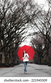 Girl with red umbrella walking in park in fall. Happy smiling multiracial Asian woman walking cheerful with red umbrella in Central Park, Manhattan, New York City, USA.