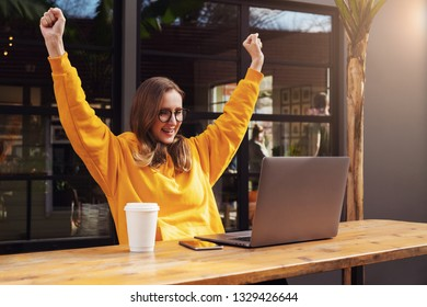 Girl rejoices in winning having raised her hands up sitting in front of laptop.Girl sitting in cafe, watches online sports match on computer.Woman blogger enjoys lot of views of her videos on Internet