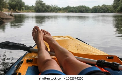 Girl is relaxation on boat  the river. Close-up of bare feet. POV