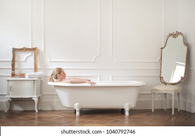 Girl relaxing in the bathtub, in a beautiful elegant room