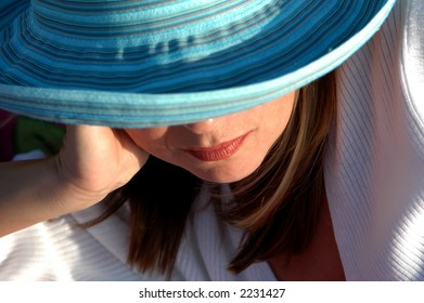Girl relaxing at beach in sun hat.