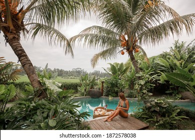 Girl relaxing and eating floating breakfast in jungle pool surrounded with palm trees on luxury villa in Bali