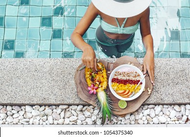Girl relaxing and eating fruit plate by the hotel pool. Exotic summer diet. Tropical beach lifestyle.