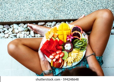 Girl relaxing and eating fruit plate by the hotel pool. Exotic summer diet. Photo of legs with healthy food by the poolside, top view from above. Tropical beach lifestyle.