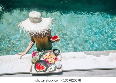 Girl relaxing and eating fruits in the pool on luxury villa in Bali. Exotic summer diet. Tropical beach lifestyle.