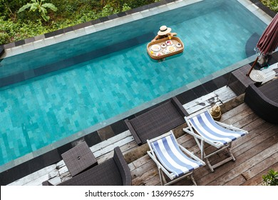 Girl relaxing and eating in luxury hotel pool. Served floating breakfast in  resort.
