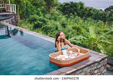 Girl relaxing and eating in luxury infinity pool with a view. Served floating breakfast in i resort.