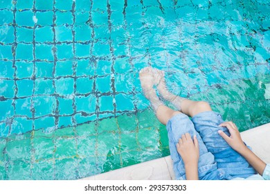 The girl relaxing feet with water in the pool.