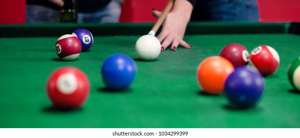 Girl is relaxing with a game of pool