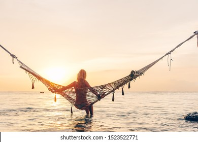 Girl relaxing in hammock at paradise island. Dreamy evening on sunset beach.