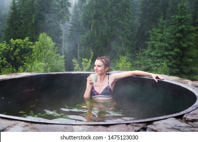 Girl relaxing in a hot vat on a background of mountain forests.