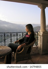 Girl relaxing in a luxurious balcony over the douro river, in the Oporto wine region, Portugal