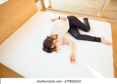 Girl relaxing on a bed,woman with curly hair,pretty face,white t-shirt,bright interior,happy face,relax,alone,skinny girl,alone home